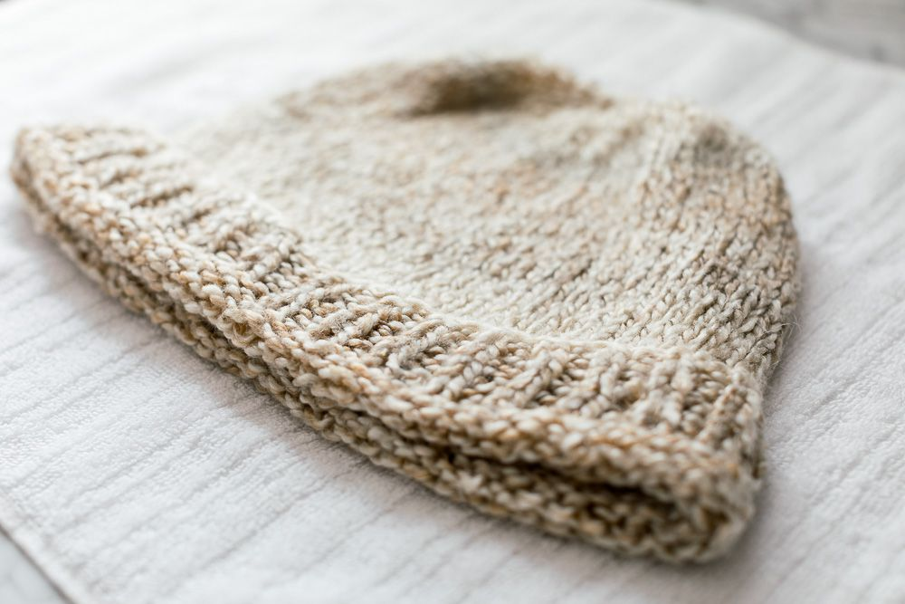 A knit hat drying on a towel
