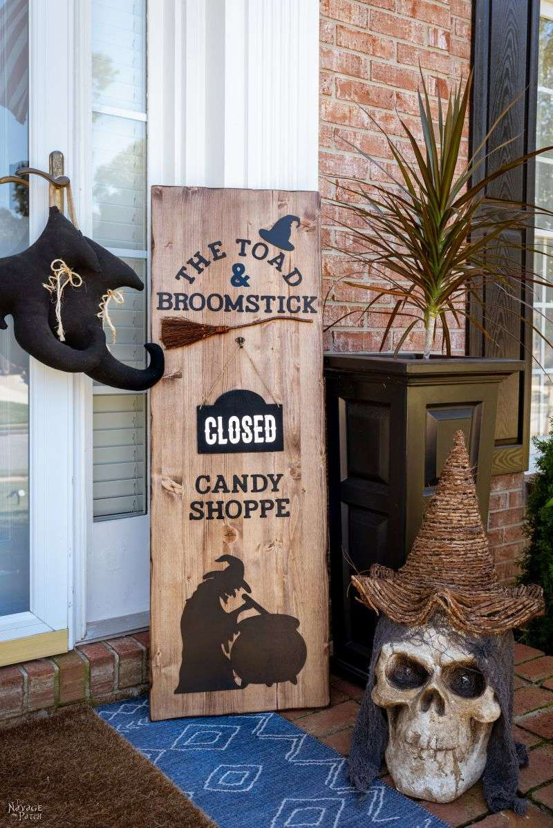 A wooden candy shop sign on a porch