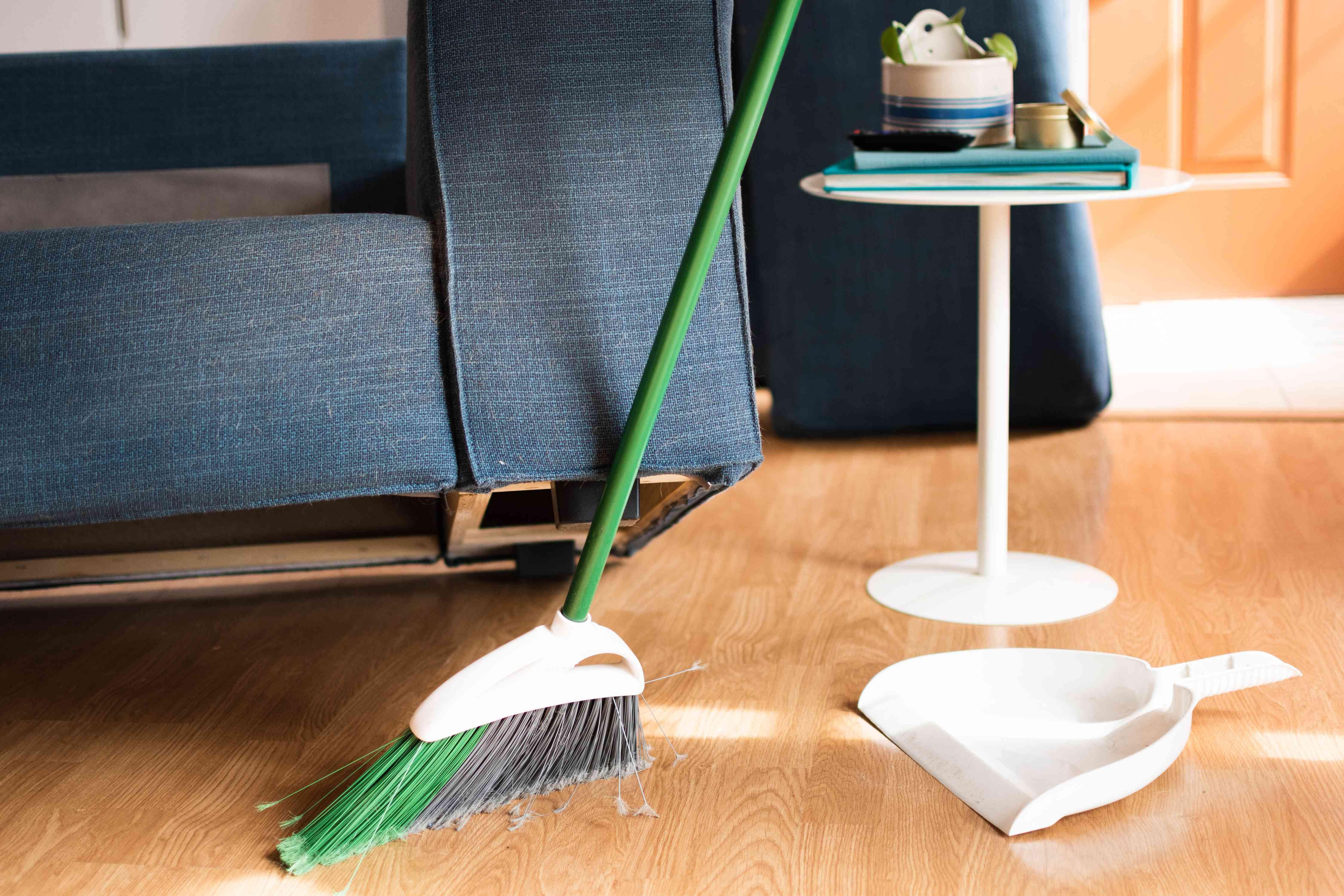 Đi văng bọc nệm màu xanh đậm được nâng lên để làm sạch sàn bằng chổi và chổi quét bụi