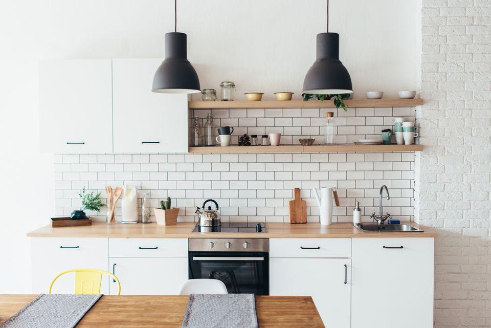 Moderno interior nuevo y luminoso de cocina con muebles blancos y mesa de comedor.