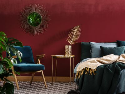 bedroom with burgundy red wall and gold with blue accents