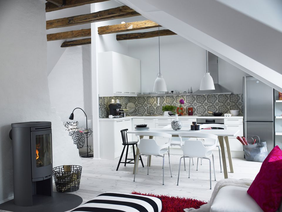 Swedish home design highlighting a white kitchen with table, chairs, pendant lights, and stainless steel appliances.