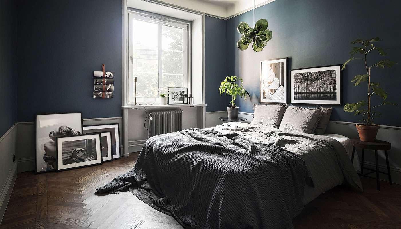 Gris ropa de cama en una habitación azul marino