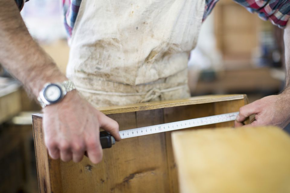 An antique furniture restorer measuring a piece of wood.