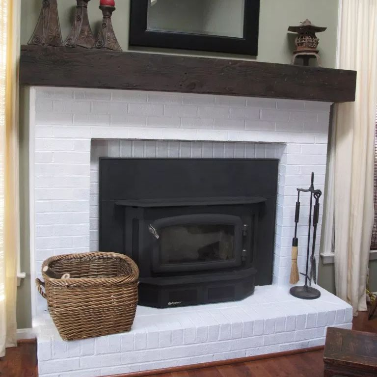 A white brick fireplace with a dark brown mantel
