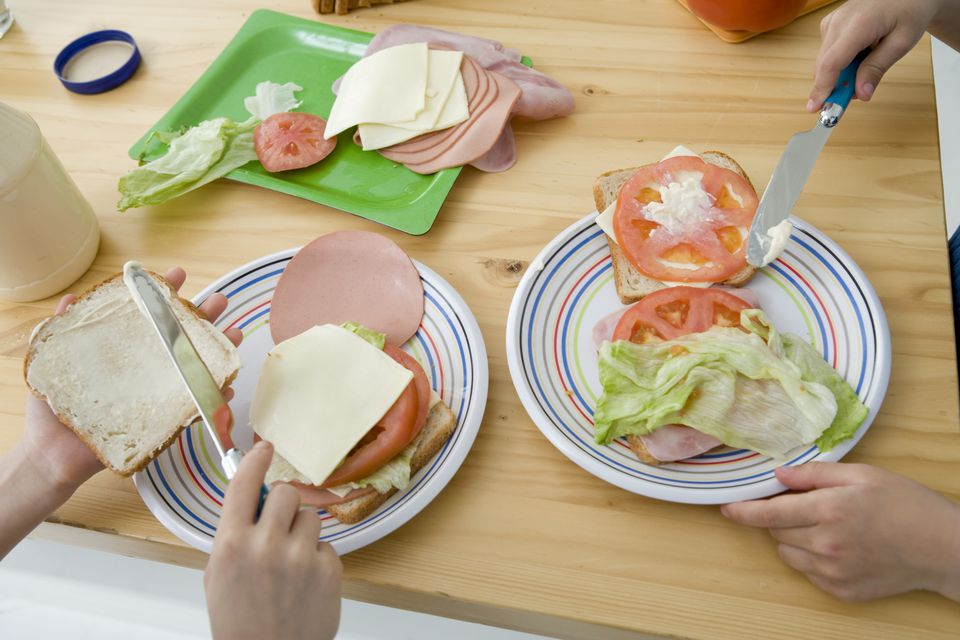Mayonnaise being spread on sandwiches