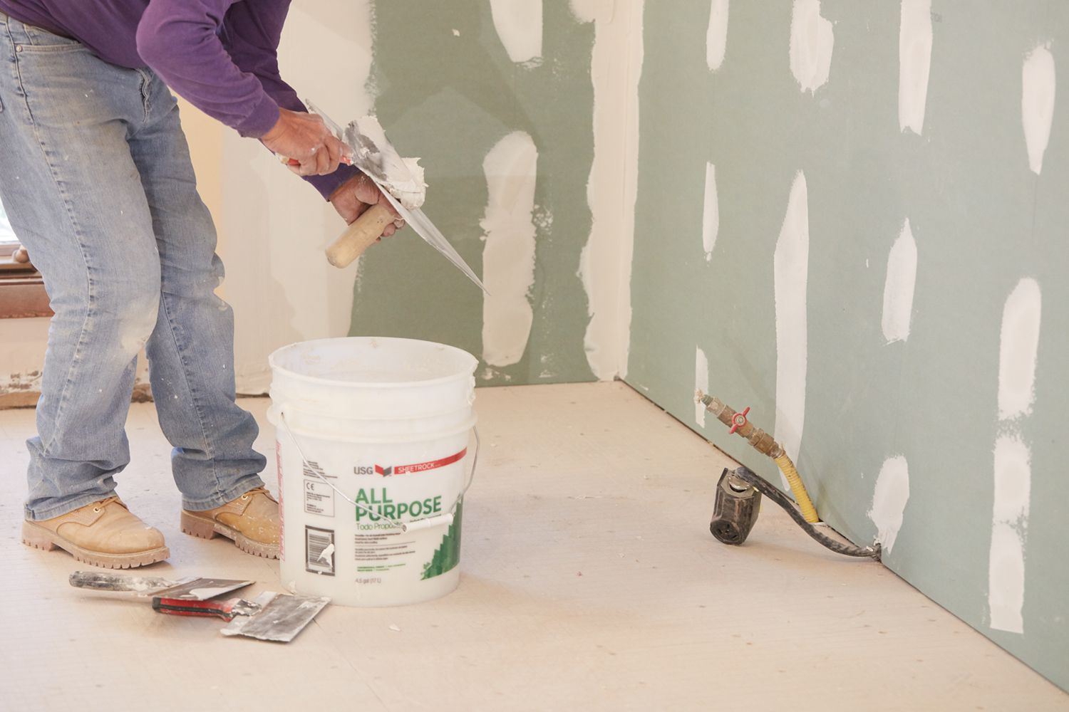 Plaster spots on wall with contractor adding more near white bucket