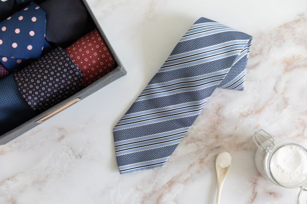 Blue striped necktie laying on white marbled surface next to glass container of baking soda and box of rolled neckties