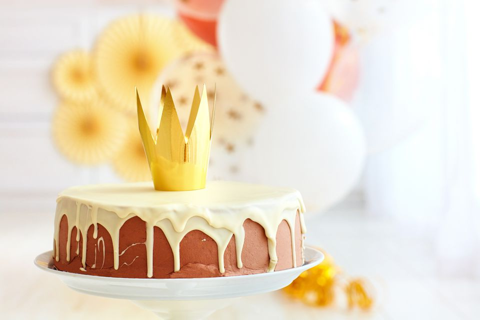 yummy birthday cake with golden crown on baby party background