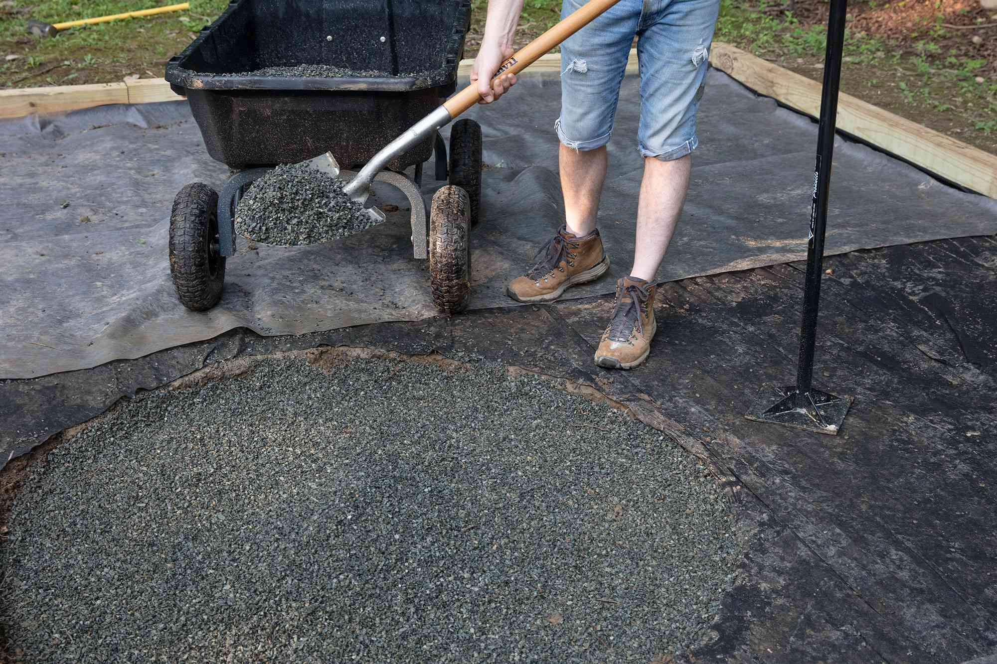 Gray drainage gravel added to circular location for fire pit with shovel