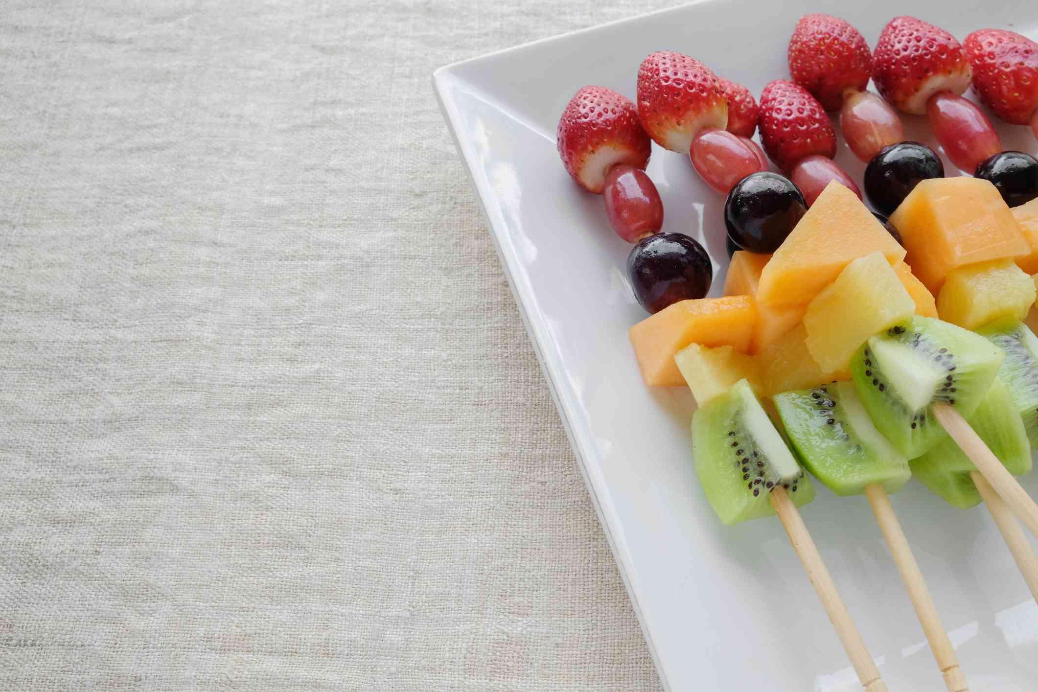 fresh rainbow fruit skewers on white plate