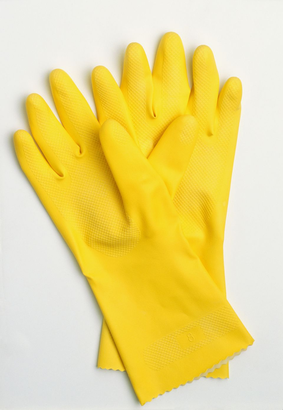 Pair of yellow rubber gloves, view from above.