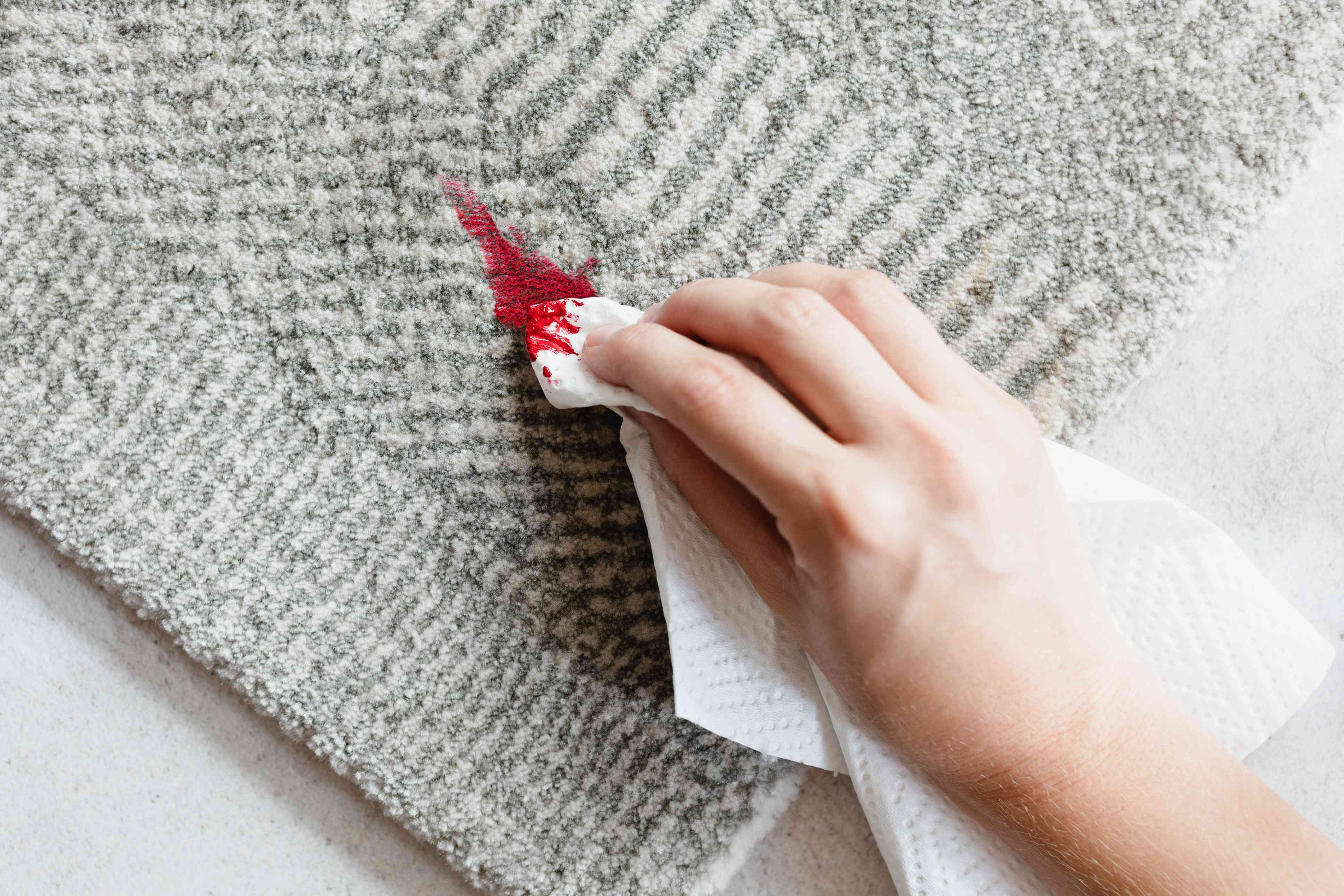 Red oil-based paint stain on gray carpet wiped with paper towel and paint thinner