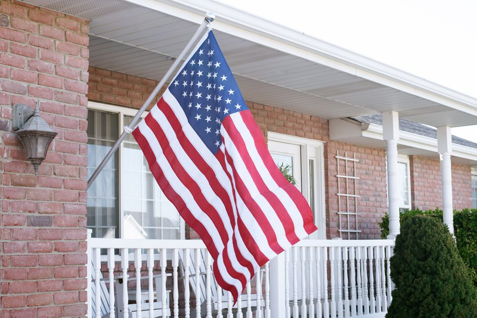 American flag hanging from pole in front of house porch