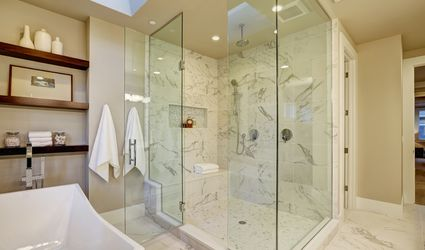 Large walk-in shower with glass doors and marble tile.