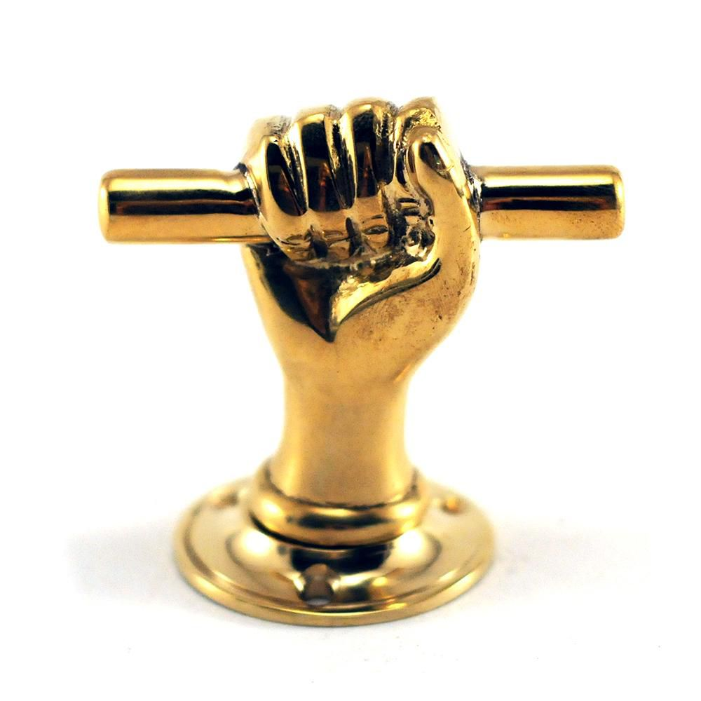 A piece of gold hardware in the shape of a hand holding a stick