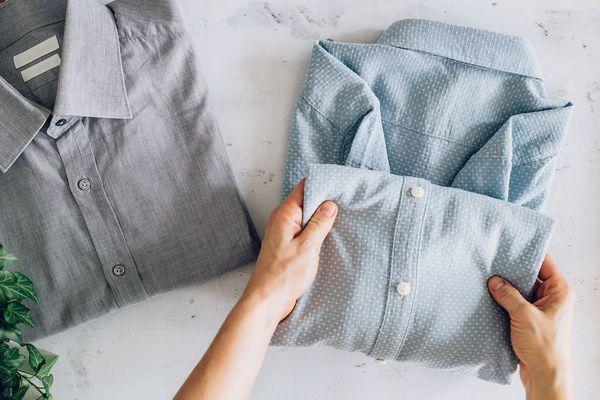 person folding a dress shirt