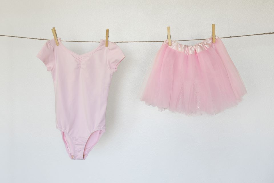Dance leotard and pink tutu hanging on clothesline with clothing pins
