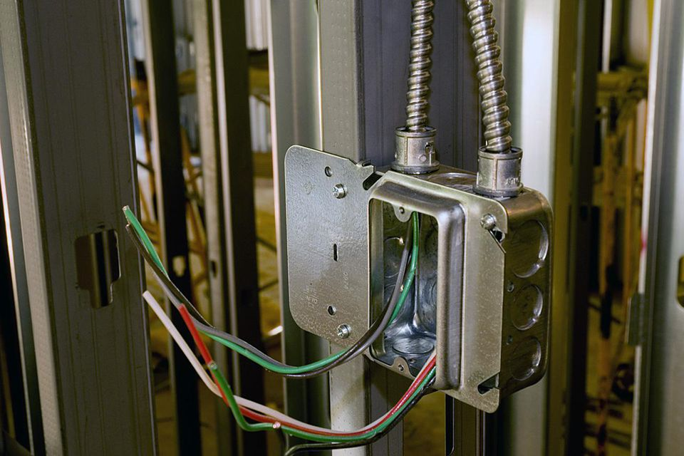 An electrical box and conduit is installed in a metal framed wall.