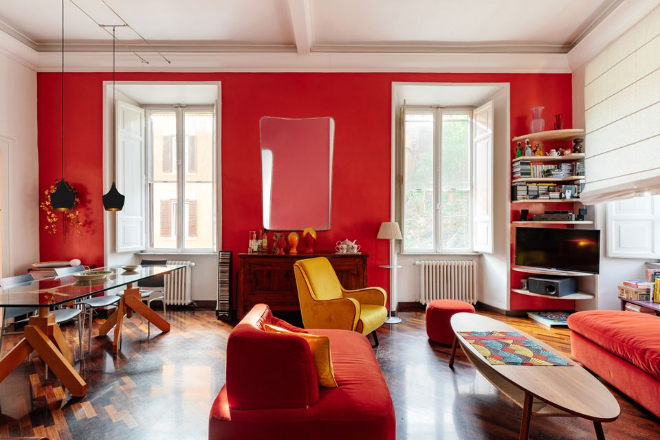Natural light filling red painted room with two windows