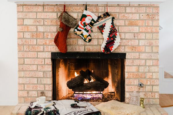 Christmas stockings hanging over brick fireplace with lighted fire