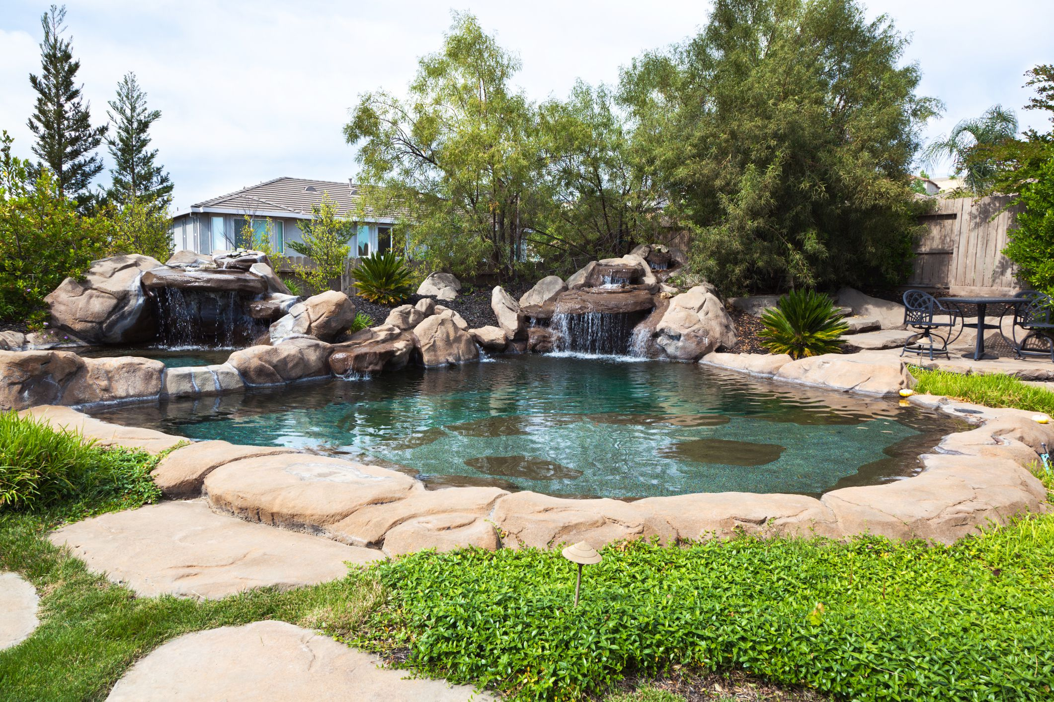 Una piscina natural rodeada de piedra y una cascada de rocas