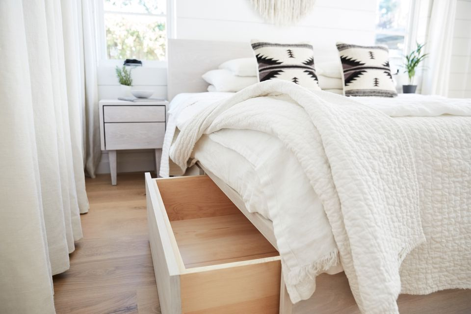 White bedroom with bed, nightstand, and drapes with under-bed storage.under bed storage