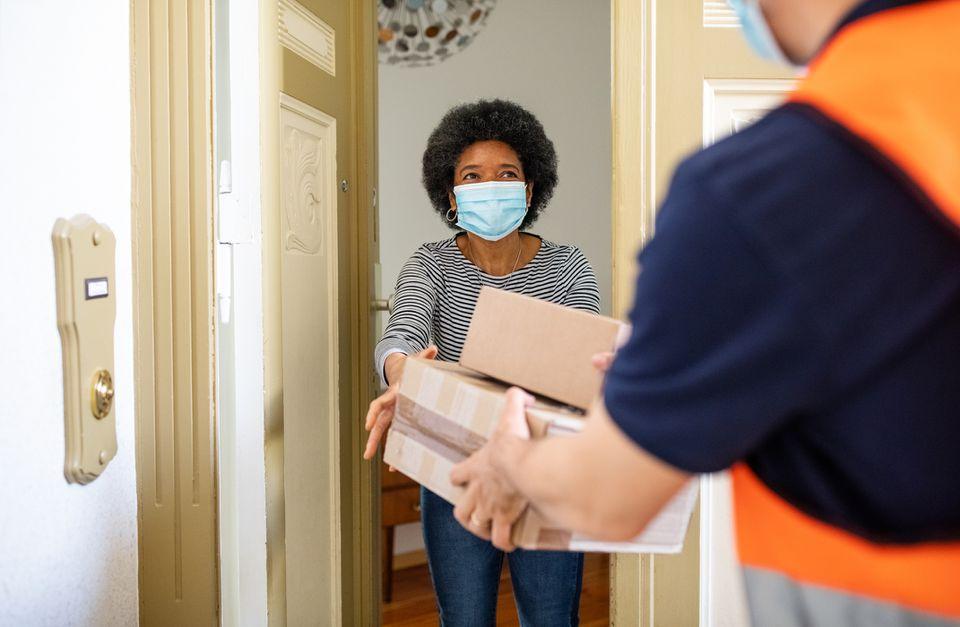 Woman receiving packages at door.