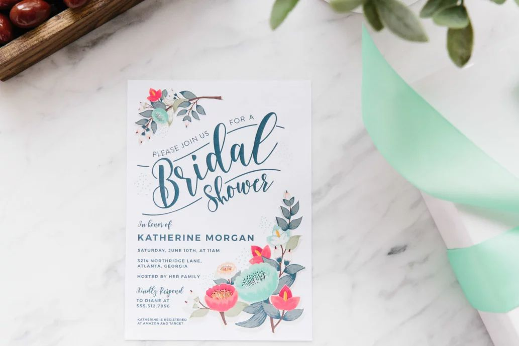 a floral bridal shower invite on a marble table