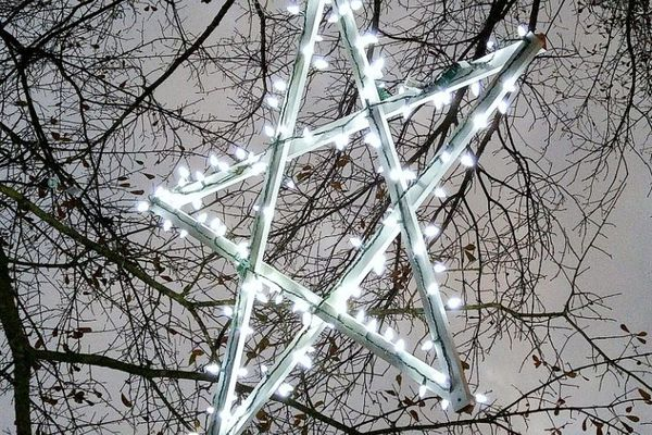A wooden lighted star hanging from a tree