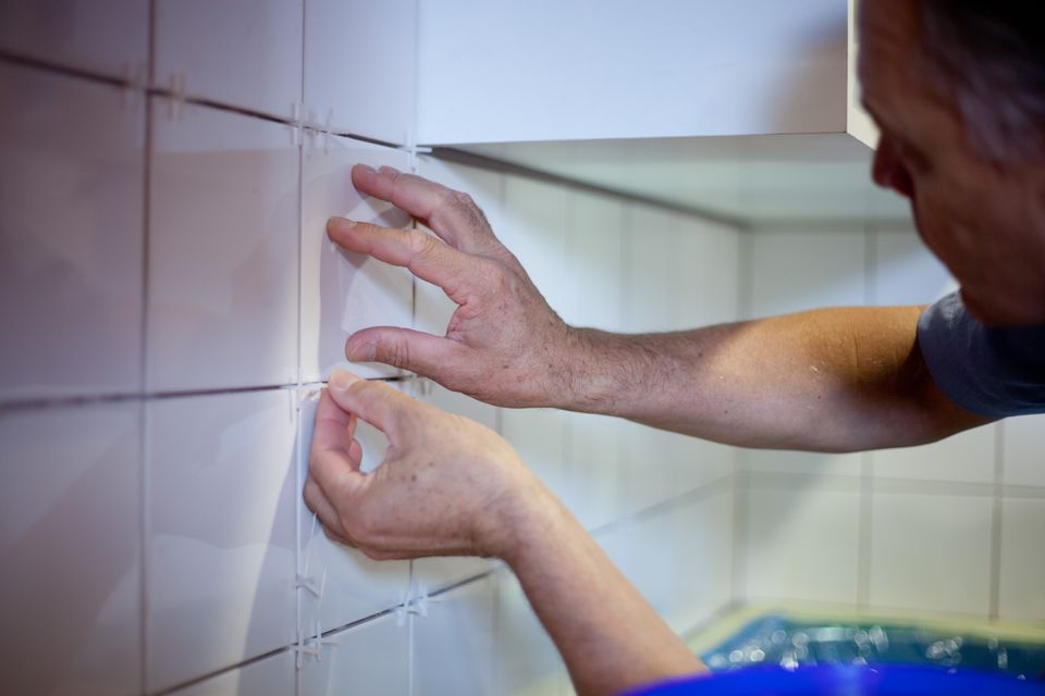 Man installing kitchen backsplash tile