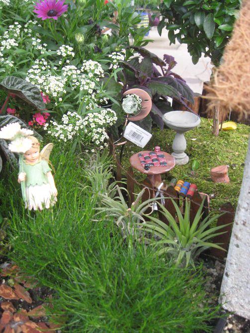 Muebles en miniatura y estatua de hadas en jardín