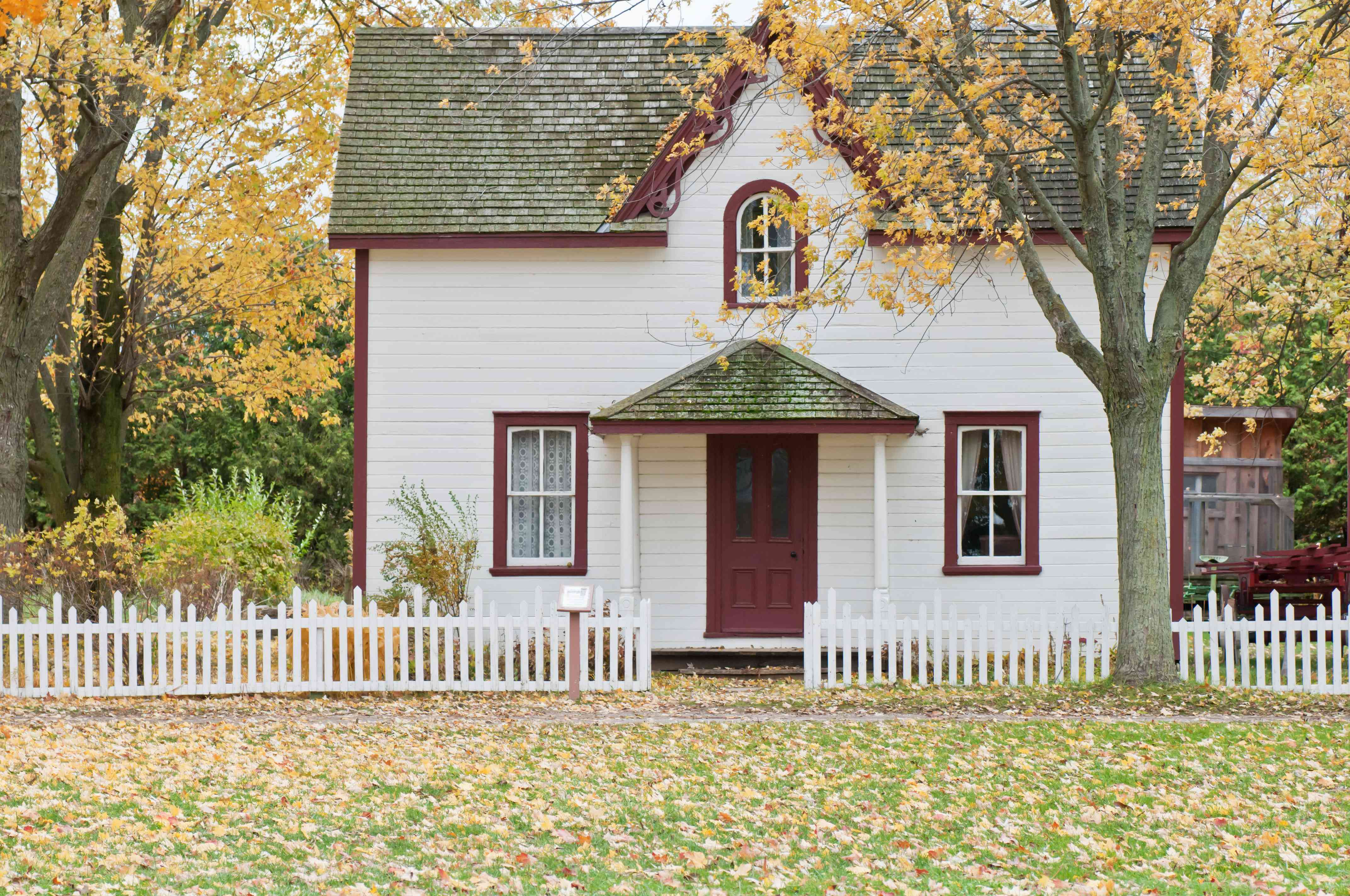 A small house with a tree and fence in the autumn