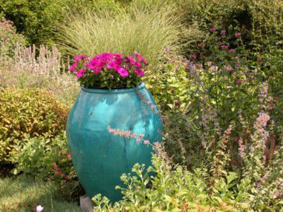 Pinkish-purple flowers in a large teal vase.