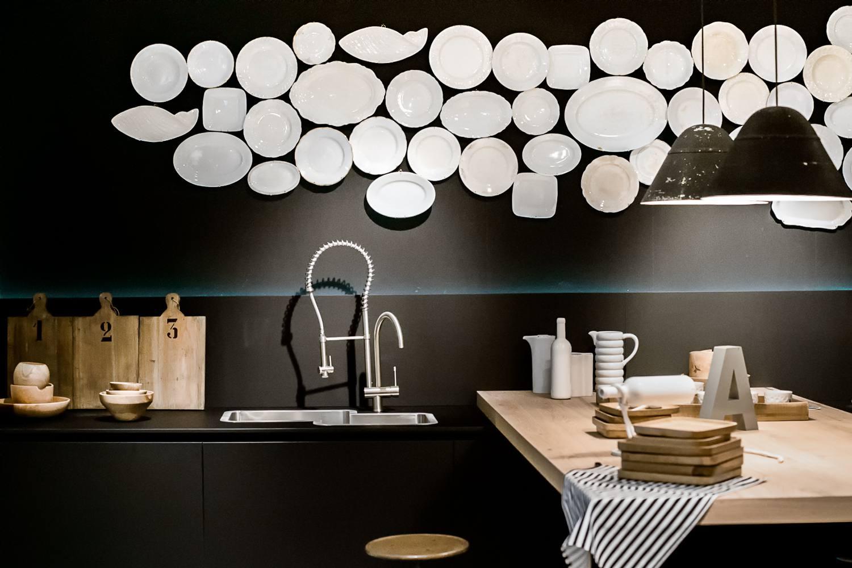 Luminarias que cuelgan sobre el mostrador de madera por el fregadero con placas en la pared