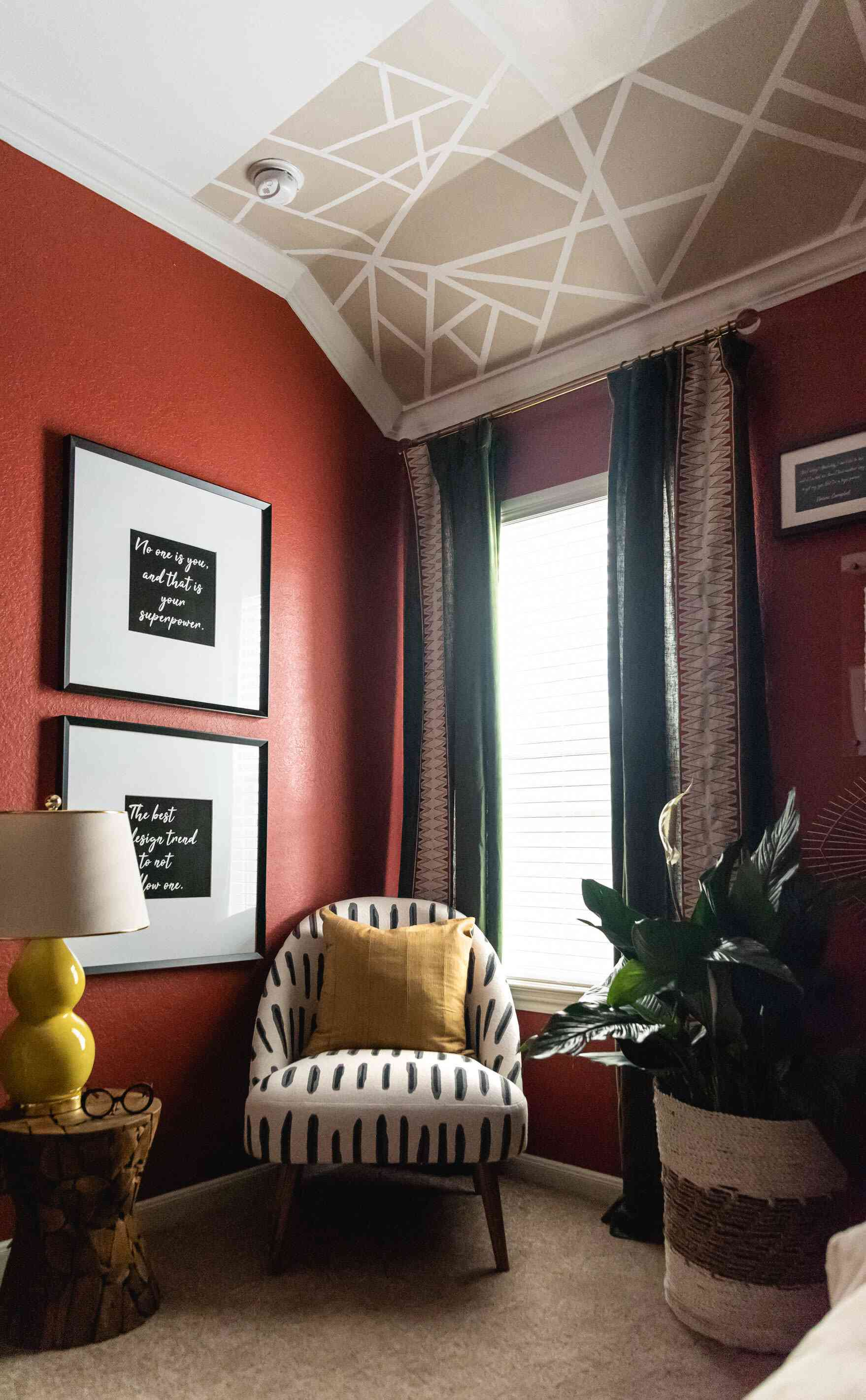 red bedroom with white and black pattern chair, red walls, mural on ceiling