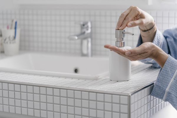 Close-up of woman wputting soap on her hands in bathroom - stock photo