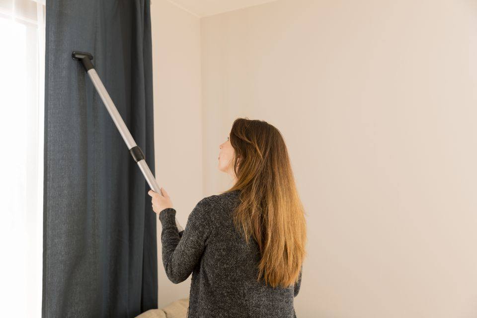 Woman using a vacuum cleaner wand to clean long blue drapes.