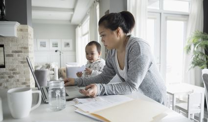 Toddler son watching mother working at laptop in kitchen
