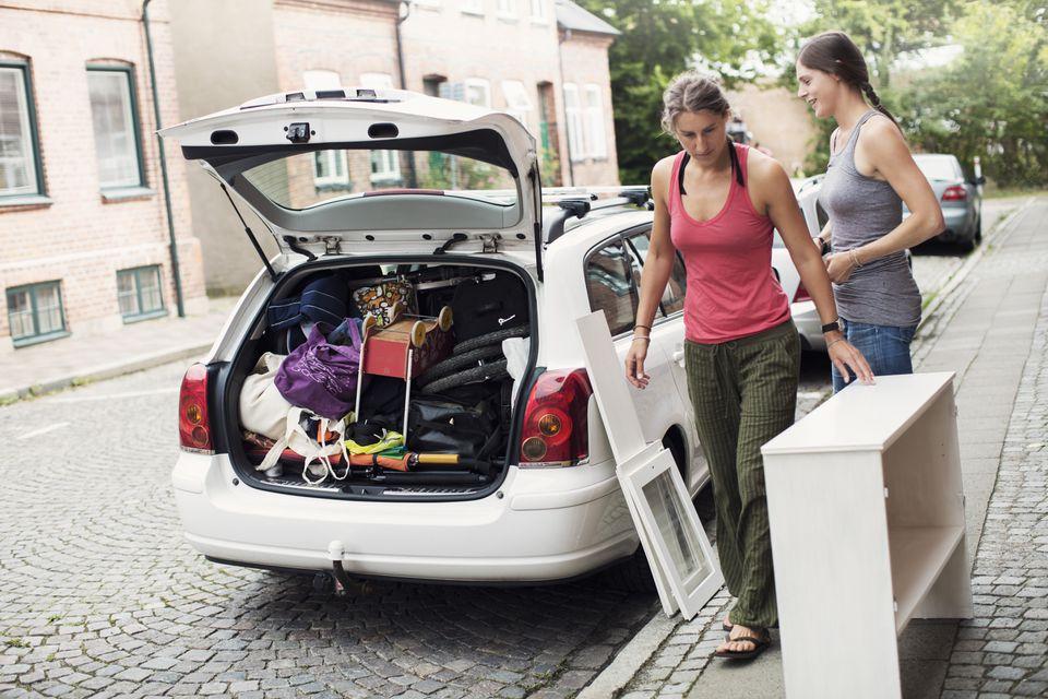 Women standing by open trunk of car on street