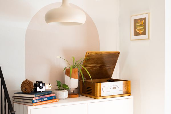 Tan-colored painted arch behind console table with record player, houseplant and books