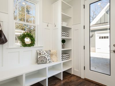 White and organized mudroom with window and windowed door