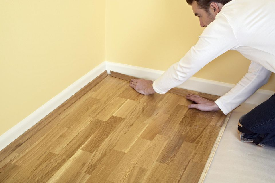 Man Holding Piece Of Quadrant On Laminate Flooring