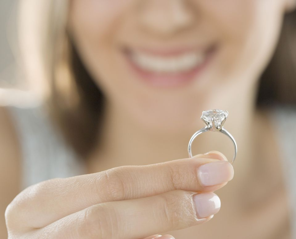 Woman holding engagement ring, close-up (focus on ring)
