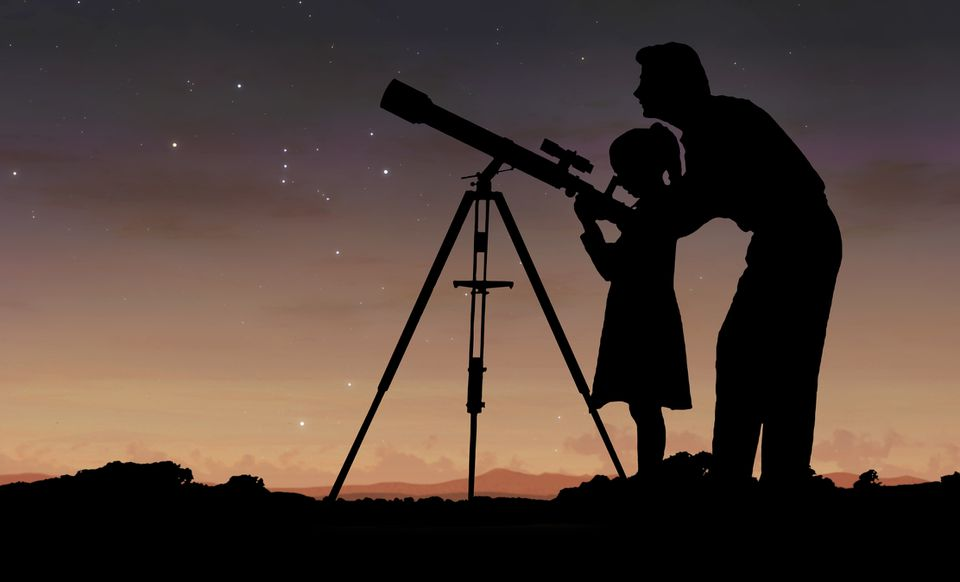 father and daughter using telescope