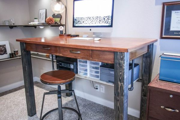 A desk with a computer on it, in an office