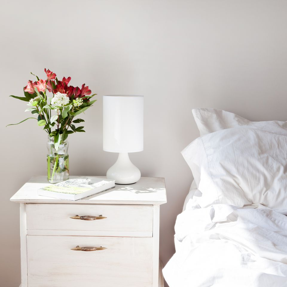 A stark white room with red and white flowers