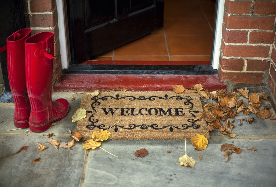 Pair of red boots next to welcome doormat