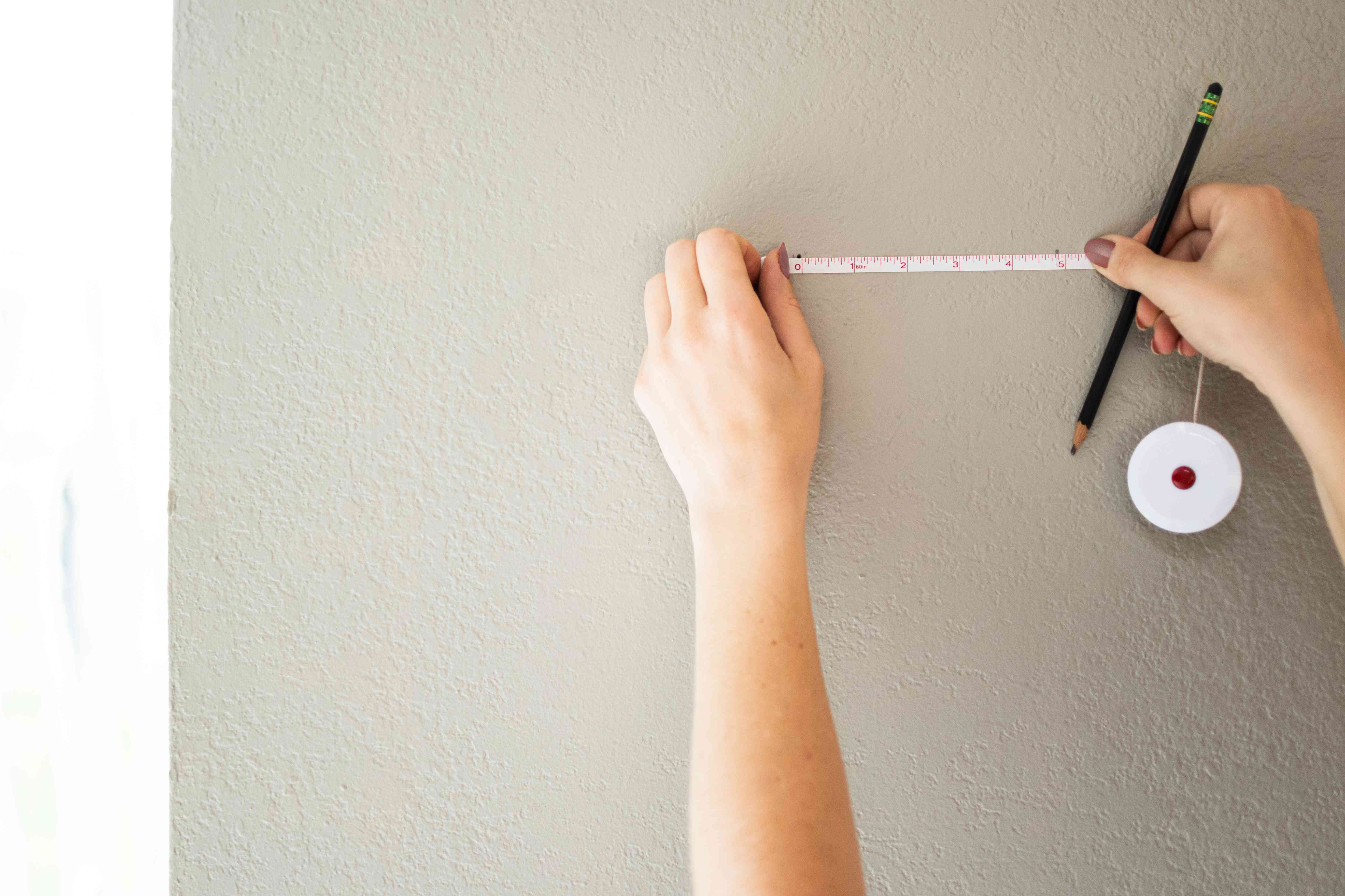 White tape measure determining marks for sawtooth hangers on wall