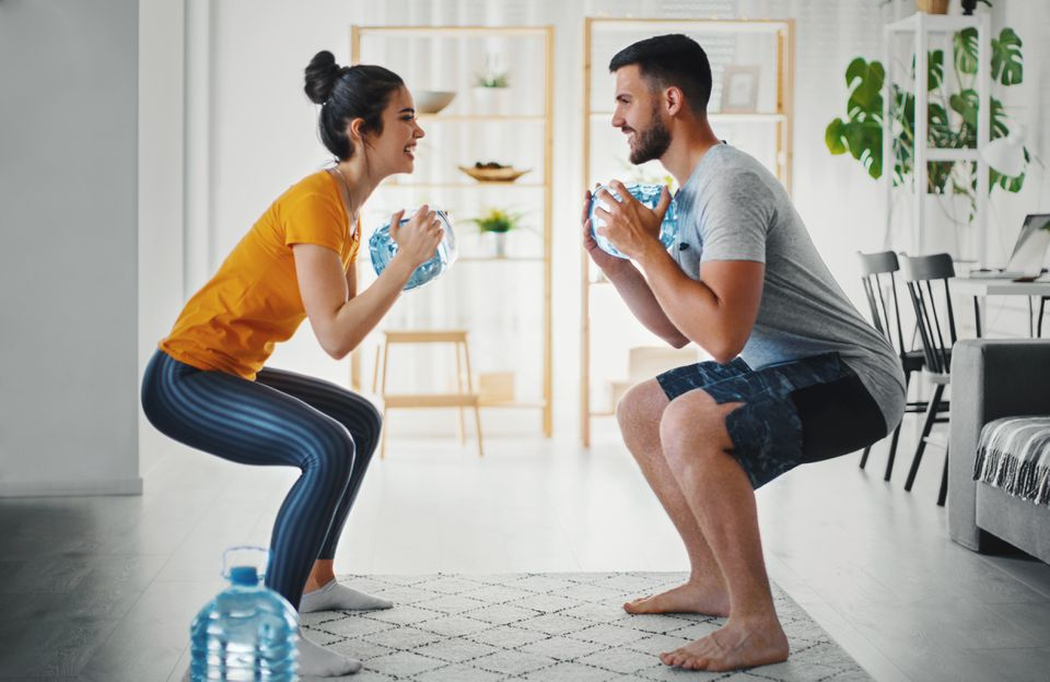 Young couple exercising with a gallon of water